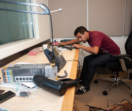 A student work on musical equipment at a radio station