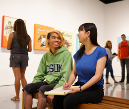 two students sit inside and talk inside the art gallery
