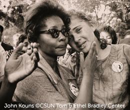 John Kouns photo of two women of color consoling each other at a march.