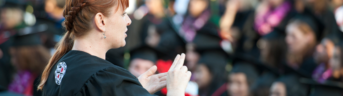 a student signs at a crowd at a commencement