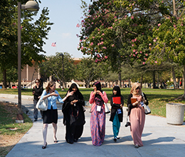 students walk across campus during the day