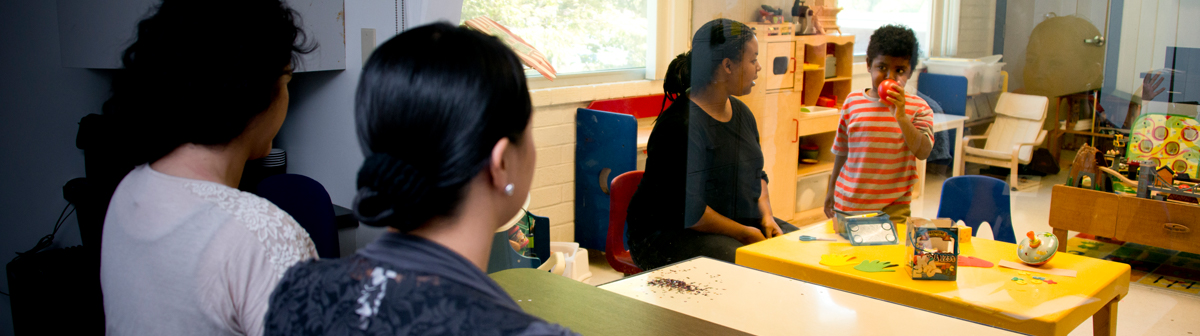 a student and a teacher watch a small child play with toys in a classroom setting