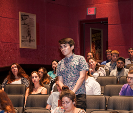 a student stands inside a theatre to speak