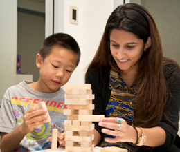 a teacher helps a small child play with blocks