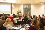 A seminar talk in a big room full of individuals.