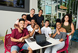 Students in front of a coffee shop smiling