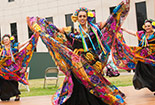 Students wearing colorful trtaditional wear dancing
