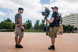 Two Students with a camera rig standing in front of Oviatt.