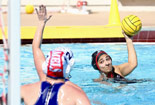 Two players mid-action in a water polo game.