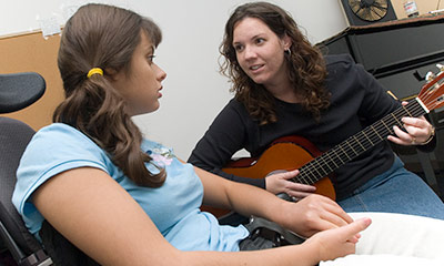 Instructor with student playing guitar.