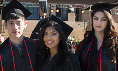 Three CSUN Students in graduation robes