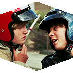 Close-up on faces of two young men in motorcycle helmets look at each other.