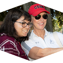 Dianne F. Harrison, wearing a CSUN hat and sunglasses, takes a selfie with a student.